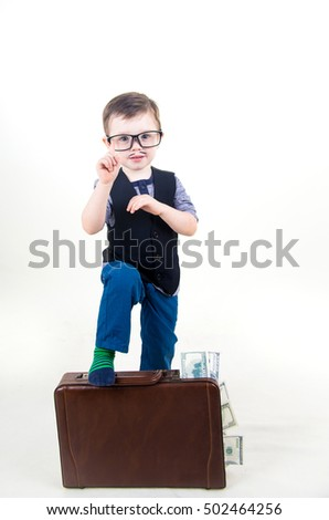 Cute little boy with a suitcase full of money.