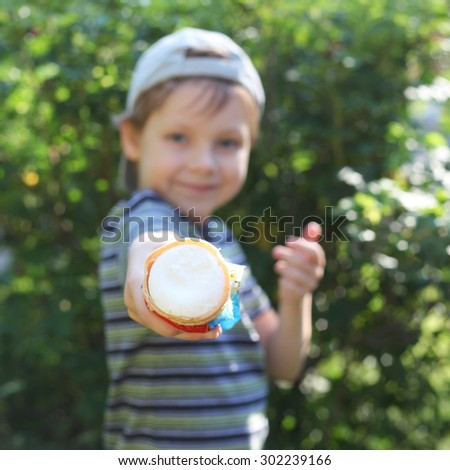 cute little boy with an ice cream outdoors, focus on the ice-cream - stock photo