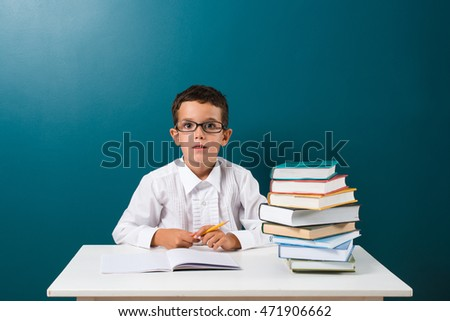 Cute little boy with books on the table, blue background