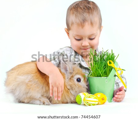 Cute little boy with Bunny and Easter eggs near basket with the green spring grass