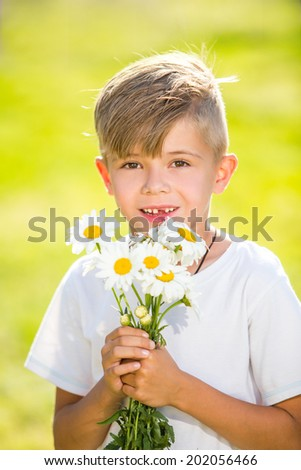 Cute little boy with flowers over green natural background. soft backlight - stock photo