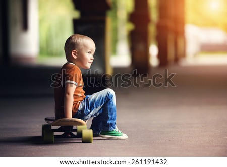 Cute little boy with his skateboard on a walk in the city - stock photo