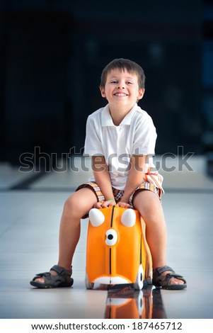 Cute little boy with orange suitcase at airport; going on holiday - stock photo