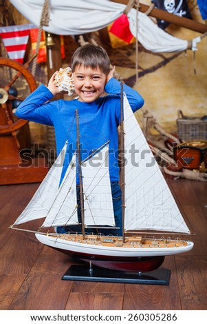 Cute little boy with ship toy on the deck of a ship - stock photo