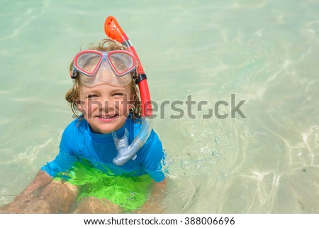 Cute little boy with snorkeling equipment at tropical beach - stock photo