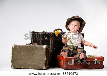Cute little boy with the flower sitting on an old suitcase. He is wearing a hat. - stock photo