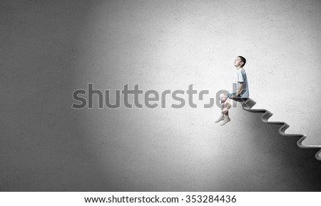 Cute little boy with toy bear sitting on ladder of books - stock photo