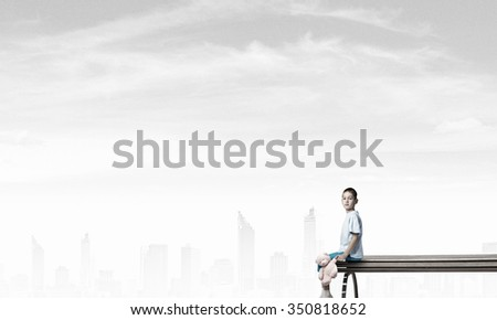 Cute little boy with toy bear sitting on wooden bench - stock photo