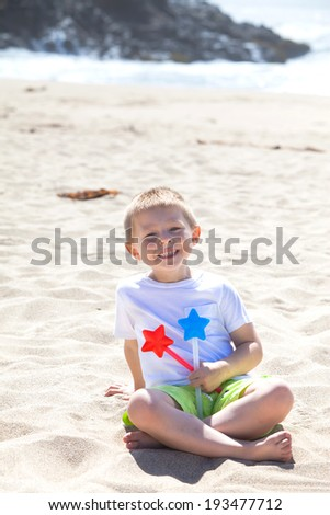 Cute little boy with two star-shaped magic wands sitting on the beach  - stock photo