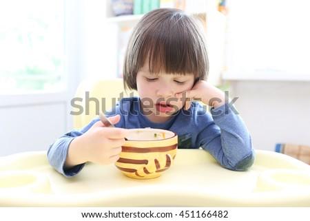 Cute little boy (2.11 years) eats soup - stock photo