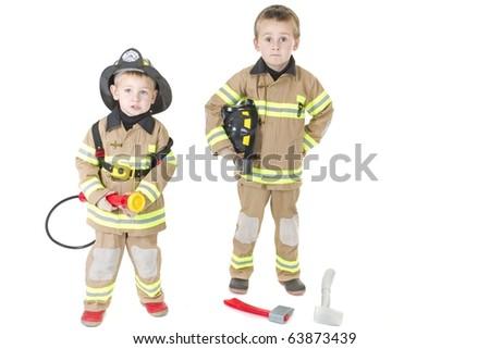 Cute little boys dressed in fire fighting uniforms - stock photo