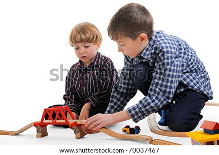 Cute little boys playing with wooden toy train - stock photo