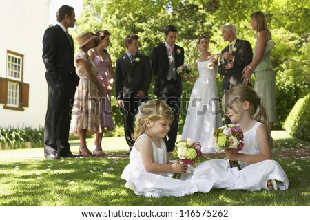Cute little bridesmaids holding bouquets with guests in background - stock photo