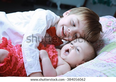 Cute little brother and sister at home, happy brother hugging his sister lying on blanket. Adorable family - stock photo