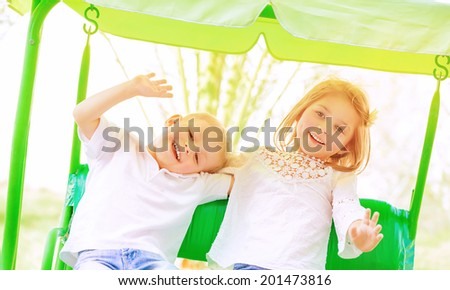 Cute little brother and sister having fun on the swing on backyard, cheerful children in daycare, love and friendship concept - stock photo