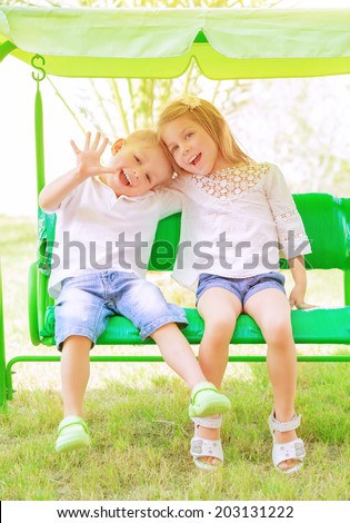 Cute little brother and sister having fun on the swing on backyard, cheerful children in daycare, love and friendship concept