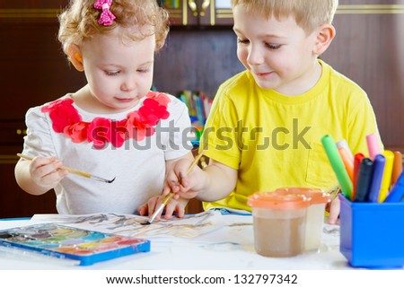 Cute little brother and sister painting at home - stock photo