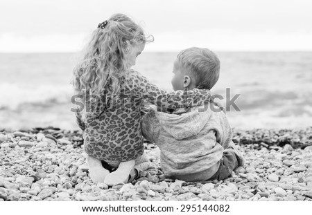 cute little brother and sister playing on the beach (  black and white ) - stock photo