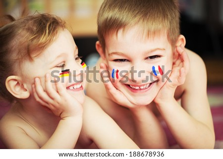 Cute little brother and sister with European flags on cheeks - stock photo
