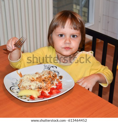 Cute little brown hair girl eating spaghetti