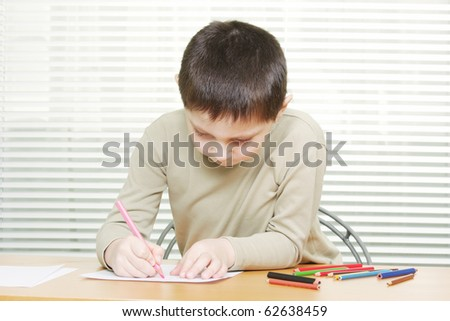 Cute little brunette boy drawing at desk with colorful crayons