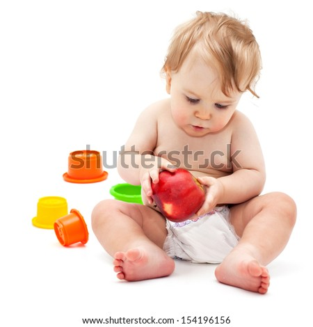 Cute little caucasian boy 11 months old sits and eats red apple on white background - stock photo