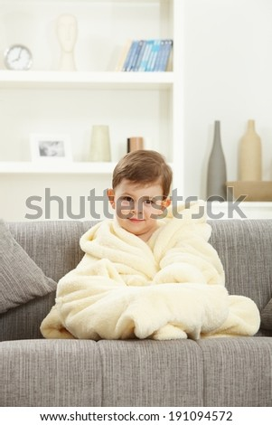 Cute little caucasian boy sitting in bathrobe after bath at home sofa. Smiling, looking at camera. Home indoor. - stock photo