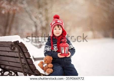 Cute little caucasian boy with teddy bear and red lantern, playing in the winter park, snowy day - stock photo