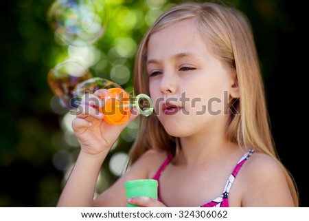 Cute little caucasian girl blowing soap bubbles - stock photo