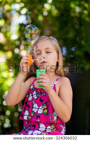Cute little caucasian girl blowing soap bubbles, innocent blissful childhood - stock photo