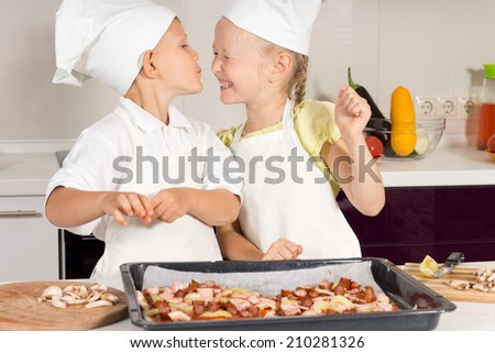 Cute Little Chef Kissing her Chef Sister in the Kitchen. Very Happy Kids. - stock photo