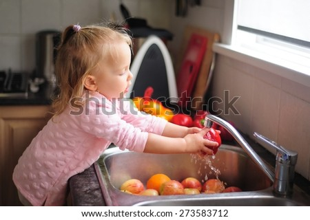 Cute little child, a toddler girl with blonde curly hair helping by washing healthy fruit and vegetables in a sink indoors in a kitchen - stock photo