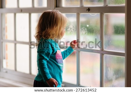 Cute little child, baby or toddler girl with adorable blonde curly hair looking out of the window on a rainy day - stock photo