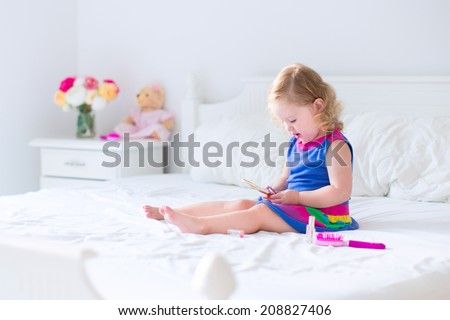 Cute little child, beautiful toddler girl with curly hair applying make up holding lipstick and mirror sitting on a white bed in a sunny bedroom playing with her toy teddy bear - stock photo