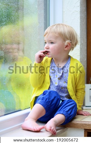 Cute little child, blonde curly toddler girl in colorful casual outfit eating chocolate sitting indoors on a rainy day looking through window with garden view - stock photo
