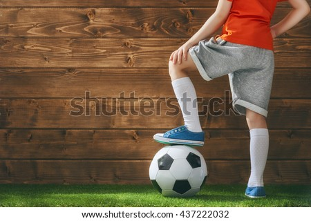 Cute little child dreams of becoming a soccer player. Child plays football.