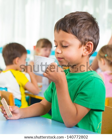 Cute little child drinking milk at kindergarten - stock photo