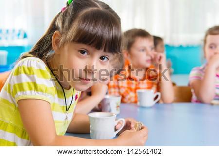 Cute little child drinking milk at kindergarten - stock photo