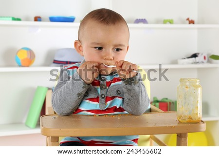 Cute little child eating baby food porridge with spoon - stock photo
