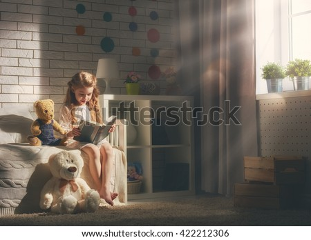 Cute little child girl reading a book. Kid girl sitting in her bed. - stock photo