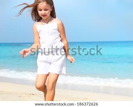 Cute little child girl running on the beach - stock photo
