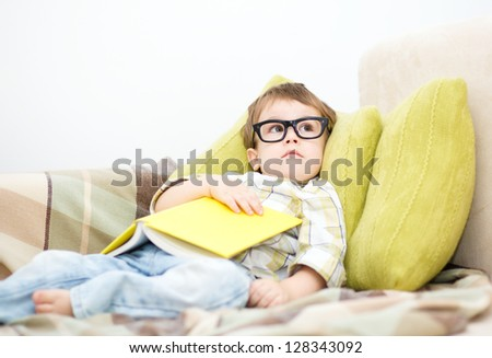 Cute little child holding a book and wearing glasses while laying on couch - stock photo