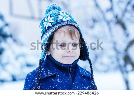 cute little child in winter clothes with falling snow. Kid enjoying and catching snowflakes, outdoors on cold day. - stock photo