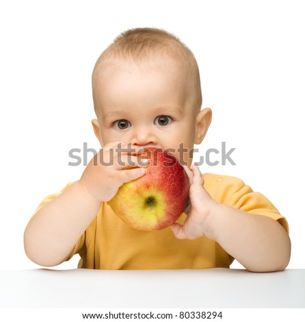 Cute little child is biting red apple while sitting at table, isolated over white