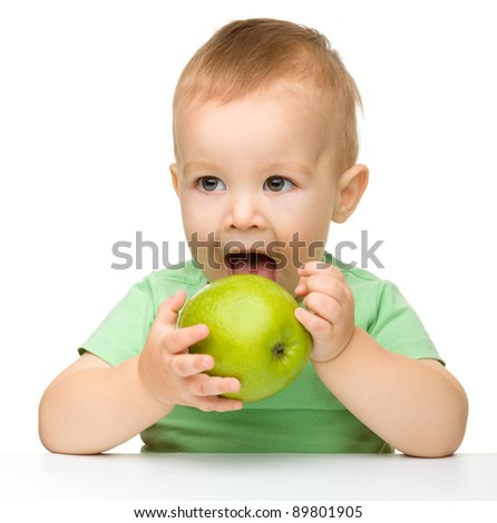 Cute little child is eating green apple while sitting at table, isolated over white - stock photo