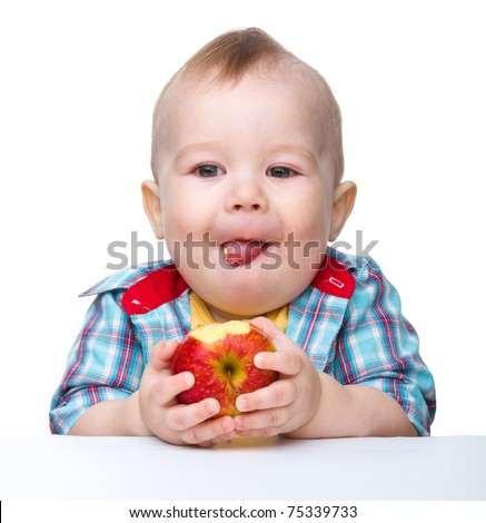 Cute little child is eating red apple while sitting at table, isolated over white - stock photo
