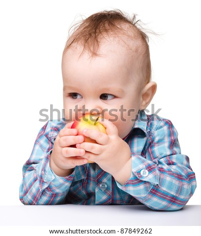 Cute little child is eating red apple while sitting at table, isolated over white