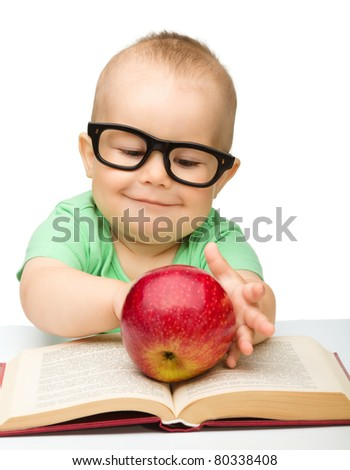 Cute little child is playing with red apple while sitting at table, isolated over white - stock photo
