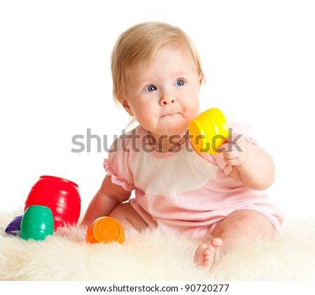 Cute little child is playing with toys while sitting on floor, isolated over white - stock photo