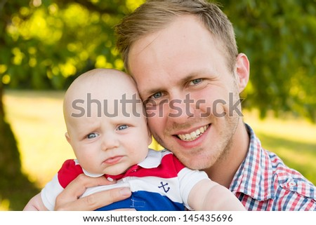 cute little child joke outdoor with dad - stock photo